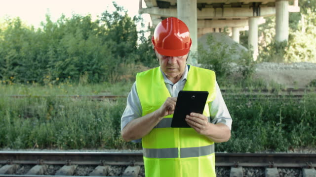 Railroader in uniform typing on the tablet at camera when checking railway video