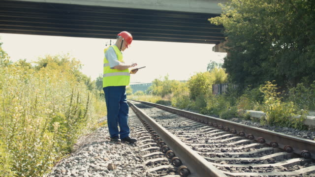 Railroader walking at the railway to check a serviceability and noting on tablet video