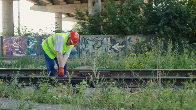Railroader walking on railway and unscrewing nuts on the rail with repair key video