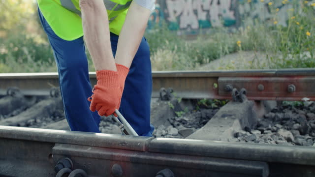 Railroader's hands unscrewing the nuts on the rail with repair key video