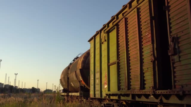 railway freight cars and tank cars on tracks overgrown with grass - wagon kolejowy filmów i materiałów b-roll