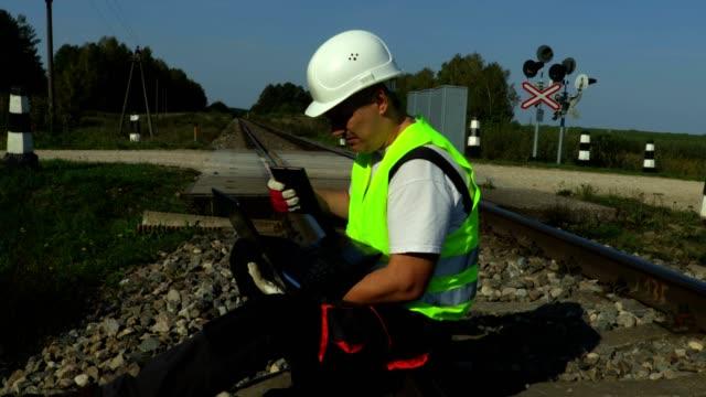 vídeos de stock, filmes e b-roll de trabalhador ferroviário usando o pc e falando pelo telefone inteligente - transporte ferroviário