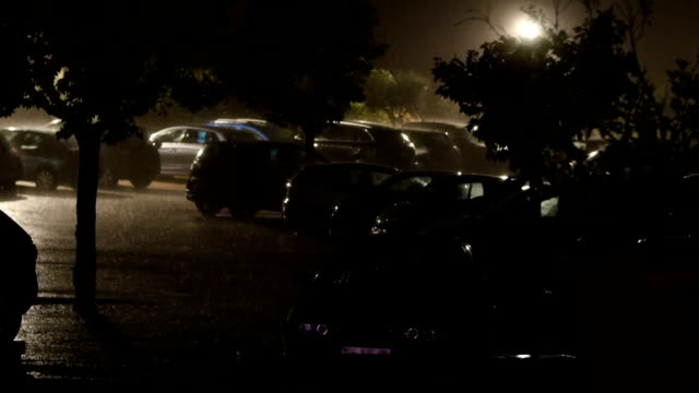 Rain and storm on a parking during night. video