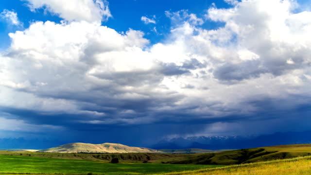 烏雲籠罩麥田, 在陽光照射的高地上。4k timelapse - 亞洲中部 個影片檔及 b 捲影像