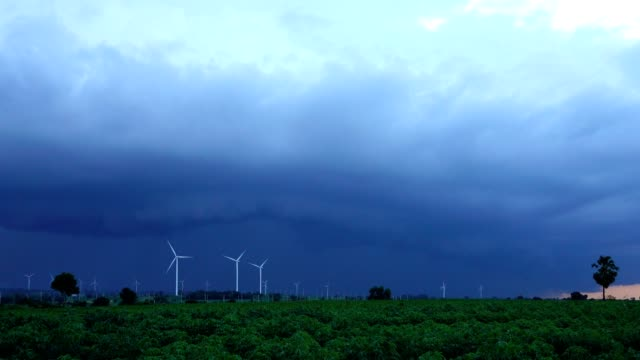 Rain coming around Wind turbines generating electricity. energy conservation concept video