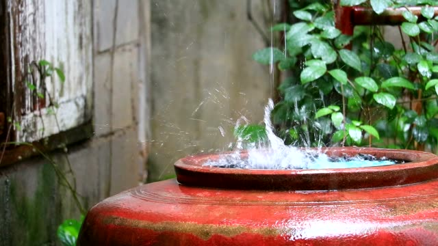 rain drop to big water jar to use in the dry season in rural of thailand - terrazza video stock e b–roll