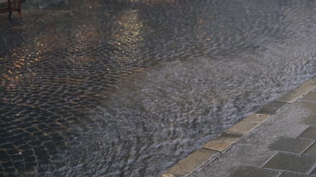 rain drops are turning into a stream of water which flowing on the pavement.