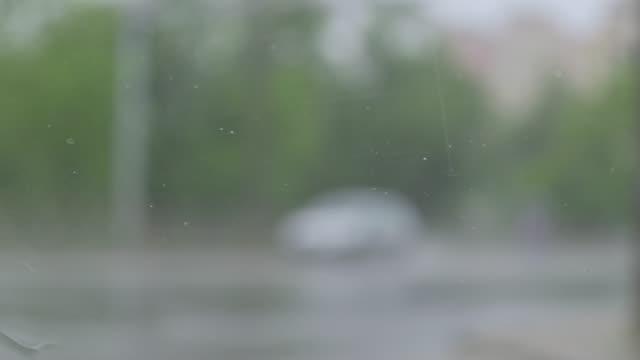regndroppar faller på bil vindrutan, suddig trafik utanför - vindruta bildbanksvideor och videomaterial från bakom kulisserna