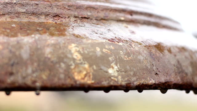 Rain drops on rusty bronze surface of ancient church bell, video