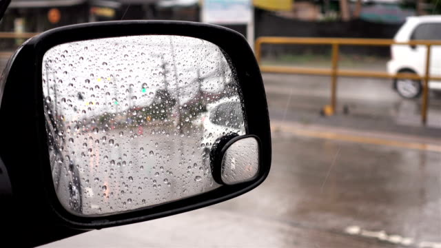 Rain drops on side mirror, Blurred of traffic in side mirror view on a rainy day video