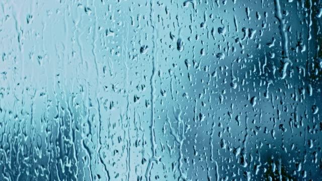Rain drops running down a window glass video
