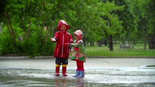 vídeos de stock e filmes b-roll de diversão de chuva - poça