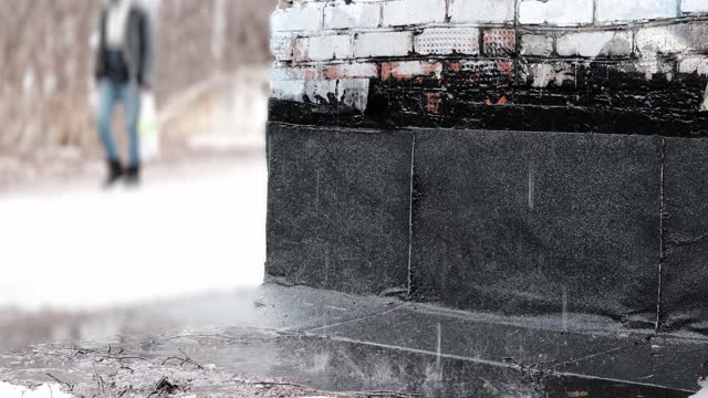 Rain is dropping on wet ground next to brick wall. Unrecognizable man is passing by on the background video