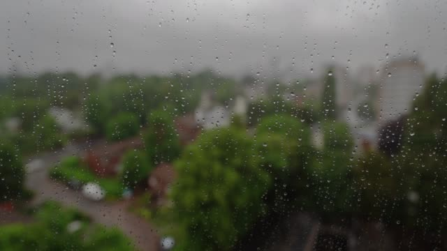 Rain on window with city background. - video