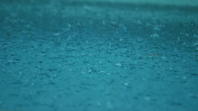 regen-tropfen spritzwasser in eine blaue pfütze - regentropfen stock-videos und b-roll-filmmaterial
