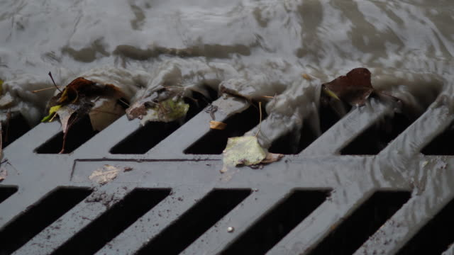 Rain water with debris flows down storm drain at the side of a street.
