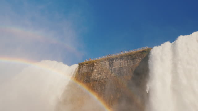 Rainbow and Niagara Falls. Two streams of water fall down, a bottom view video