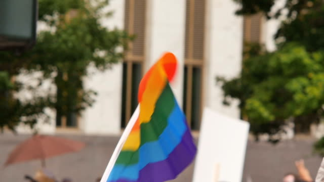 A rainbow flag waves as people walk by in the background with other rainbow flags and protest signs. A rainbow flag waves as people walk by in the background with other rainbow flags and protest signs during gay pride GLBT LGBT festival gay man stock videos & royalty-free footage