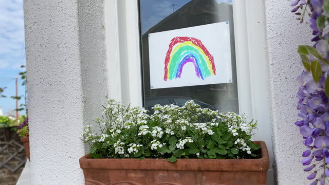 Rainbow in Window - Animated Window Poster Child's Drawing Kid's Drawn picture in window of house, animated. A rainbow grows and ripples with motion. Felt tip pens on white paper. Picture is taken down at end to show it's all over. Coronavirus cured and moving on. nhs stock videos & royalty-free footage