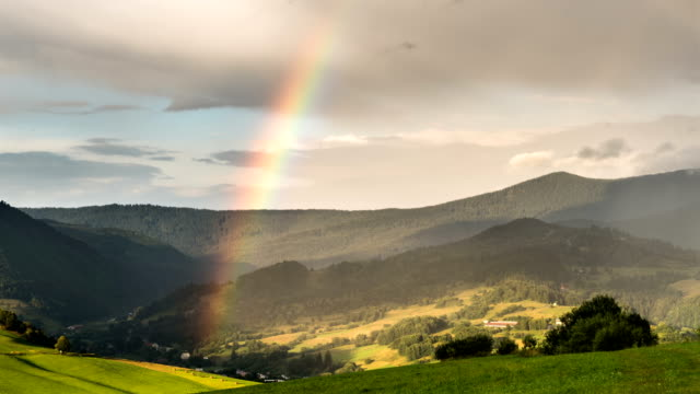 Rainbow over green rural landscape Time lapse