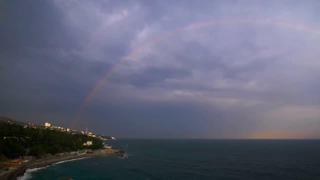 Rainbow over the sea against the backdrop of an overcast sky video