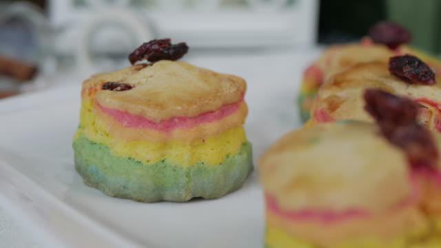 rainbow scones cake set on table. - scone filmów i materiałów b-roll