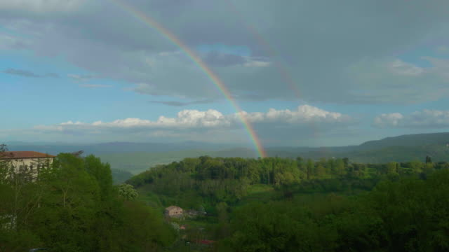 Rainbow that ends its run amid the trees of a hill in Chianti. Montepulciano
