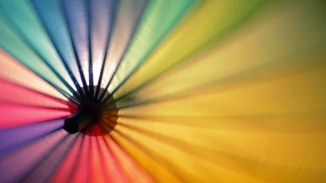 vídeos de stock e filmes b-roll de rainbow umbrella spinning - guarda chuva