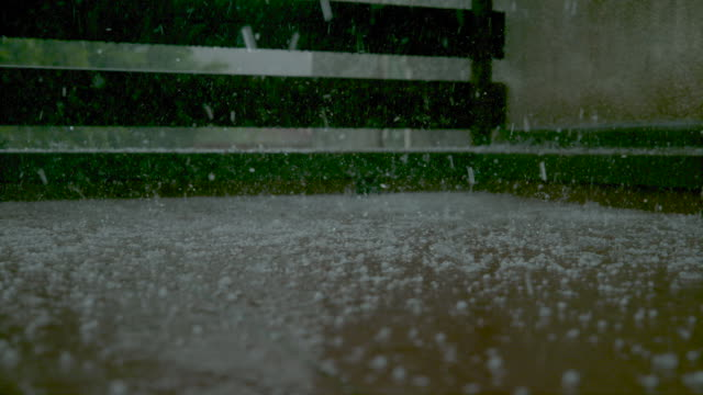 close up: raindrops and soft hail fall onto the wet porch and splash still water - grandine video stock e b–roll