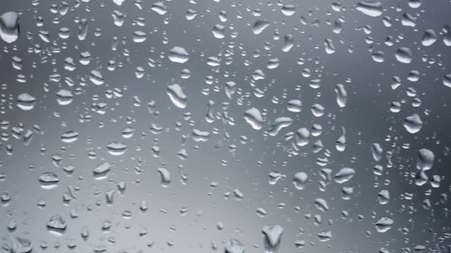 raindrops falling down a window video