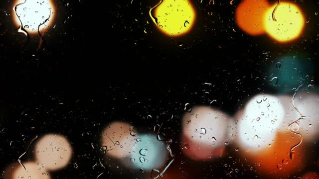 通りの信号の背景をぼかしで車の窓を雨滴 ビデオ