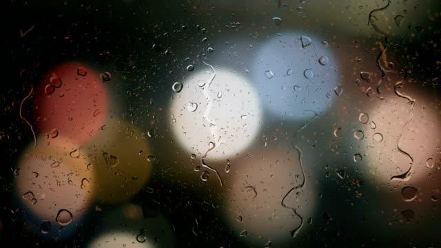 vídeos de stock e filmes b-roll de raindrops on a car window with blurred background of street traffic lights - carro na rua