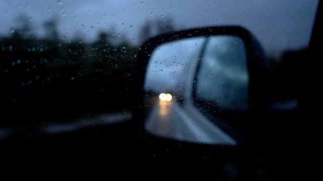 SLO MO Raindrops on the side mirrors of the car at night