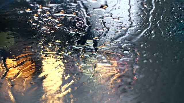 Gotas de chuva no pára-brisas e círculos coloridos Bokeh. Semáforo Vermelho Amarelo - vídeo