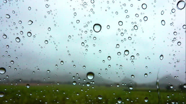 Raindrops on window in car at Mountain background. video