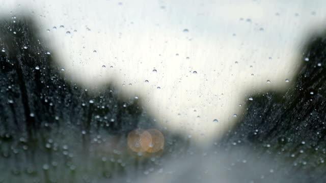 vidéos et rushes de les gouttes de pluie ruissellent le long du pare-brise de la voiture mobile sur la route - pare brise