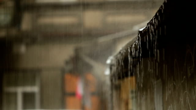 raining. he hits the roof. the water is draining. downpour in the city. - monsone video stock e b–roll