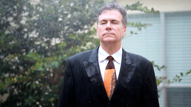 Raining on Me A sudden rain shower drenches a weary businessman with no umbrella for protection. drenched stock videos & royalty-free footage