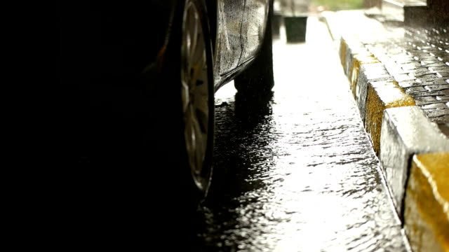 Rainy day in city streets, water drops, puddles, car passing by, super slow motion, selective focus. video
