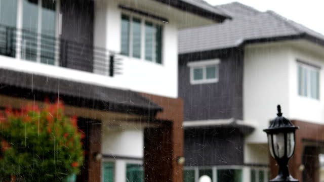 rainy day scene, focus rain falling in sky with blur house background video