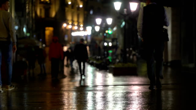 Rainy evening in the city, street with street lights, shiny asphalt from the rain. Unrecognizable pedestrians, young people. Concept lifestyle of night modern city. Cars passing by pedestrians video