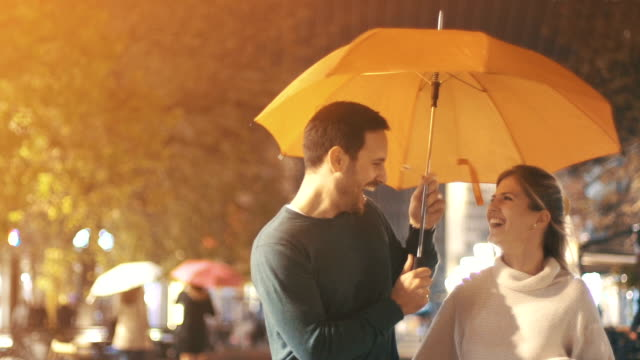vídeos de stock e filmes b-roll de rainy romantic night, slow motion. - guarda chuva