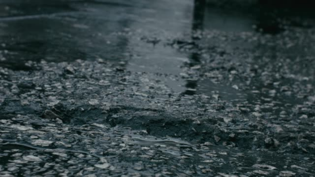 Rainy weather with physical sound of rain and an asphalt road with pebbles,  gravel, water ponds and raindrops video