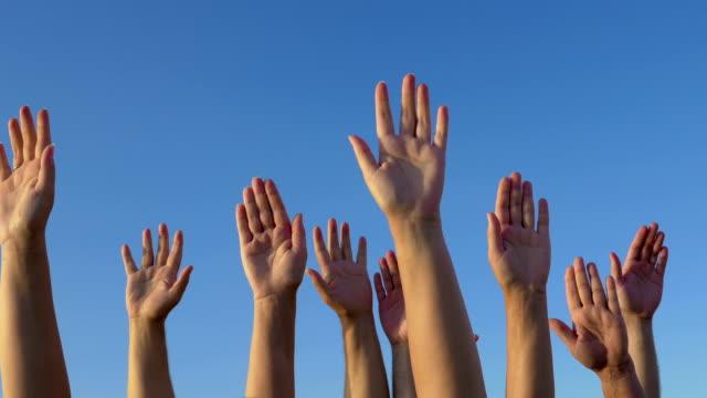 Raised hands against blue sky video
