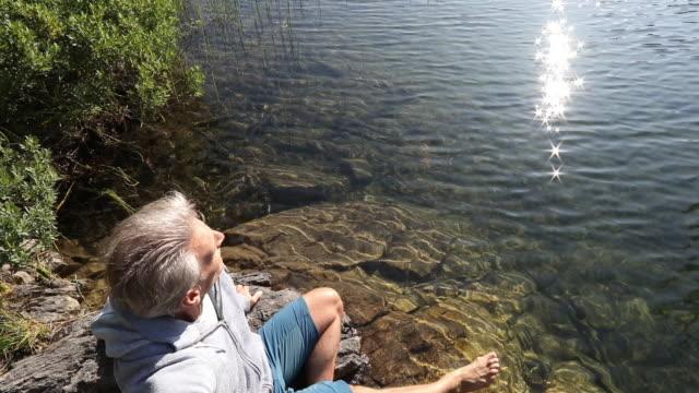 upphöjd utsikt över man koppla av på lakeshore vid sunrise - endast en medelålders man bildbanksvideor och videomaterial från bakom kulisserna