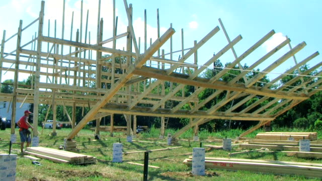 Raising a Barn Carpenters work to help put bent in place while raising a barn. barns stock videos & royalty-free footage