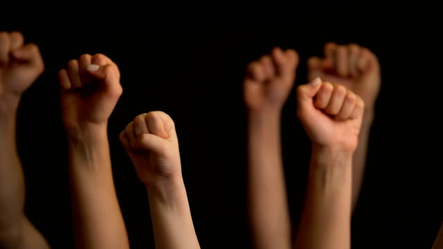 raising hands with fists on black background - бунтарство стоковые видео и кадры b-roll
