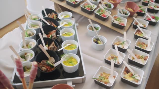 vídeos de stock, filmes e b-roll de ramekins e pequenos pratos de comida salgada na mesa buffet - festas no escritório