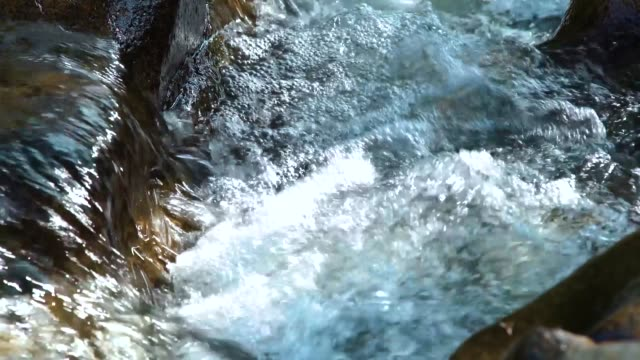 Rapid river water flowing between large stones creating white bubbling foam. Water stream flowing among stones in mountain river. Natural landscape