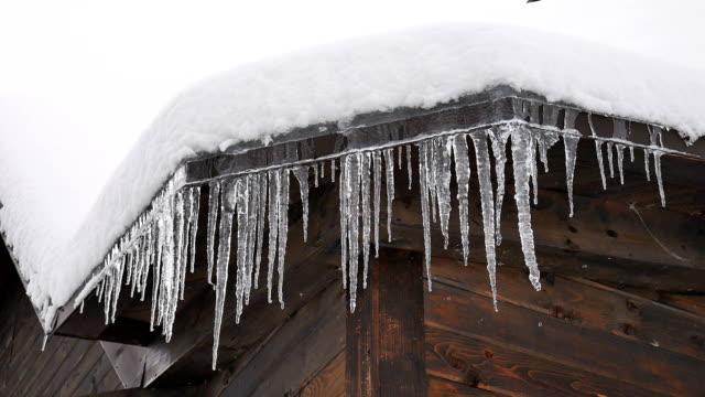 snabbt smältande långa istappar på ett snötäckt tak. väntar på ett vårkoncept - roof farm bildbanksvideor och videomaterial från bakom kulisserna